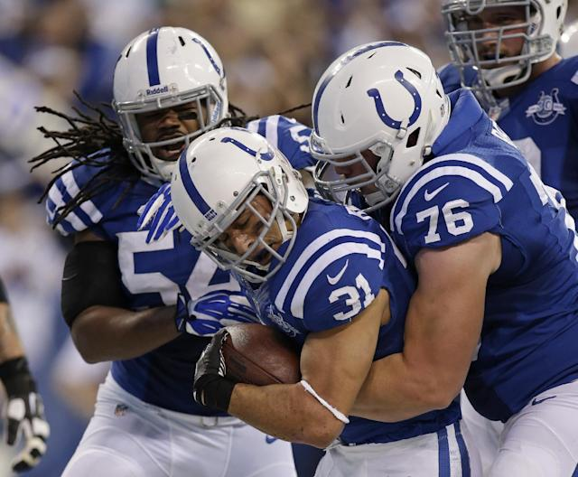Indianapolis Colts' Donald Brown (31) celebrates with teammates Mario Harvey (54) and Joe Reitz (76) following a 4-yard touchdown run during the second half of an NFL football game against the Tennessee Titans, Sunday, Dec. 1, 2013, in Indianapolis. (AP Photo/AJ Mast)