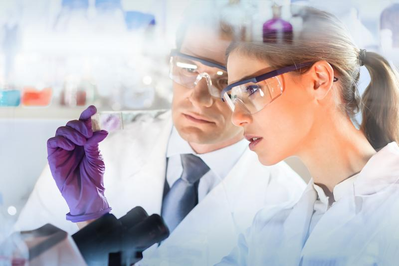 A man and woman in lab coats and safety goggles looking at a microscopic slide.
