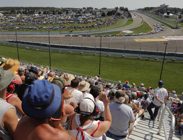 "FILE - In this Aug. 5, 2018, file photo, spectators watch as drivers come around Turn 1 during a restart after a caution during a NASCAR Cup Series auto race in Watkins Glen, N.Y. Three months after its opening day was canceled by the coronavirus pandemic, Watkins Glen International is hosting car clubs again as NASCAR weekend looms in mid-August. Everybody is excited about getting back in the saddle. I know we are,"" track president Michael Printup said. (AP Photo/Julie Jacobson, File)"