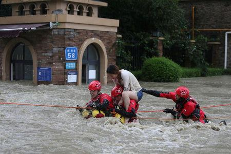 Firefighters rescue a stranded woman on a flooded street, following heavy rainfall in Chengdu