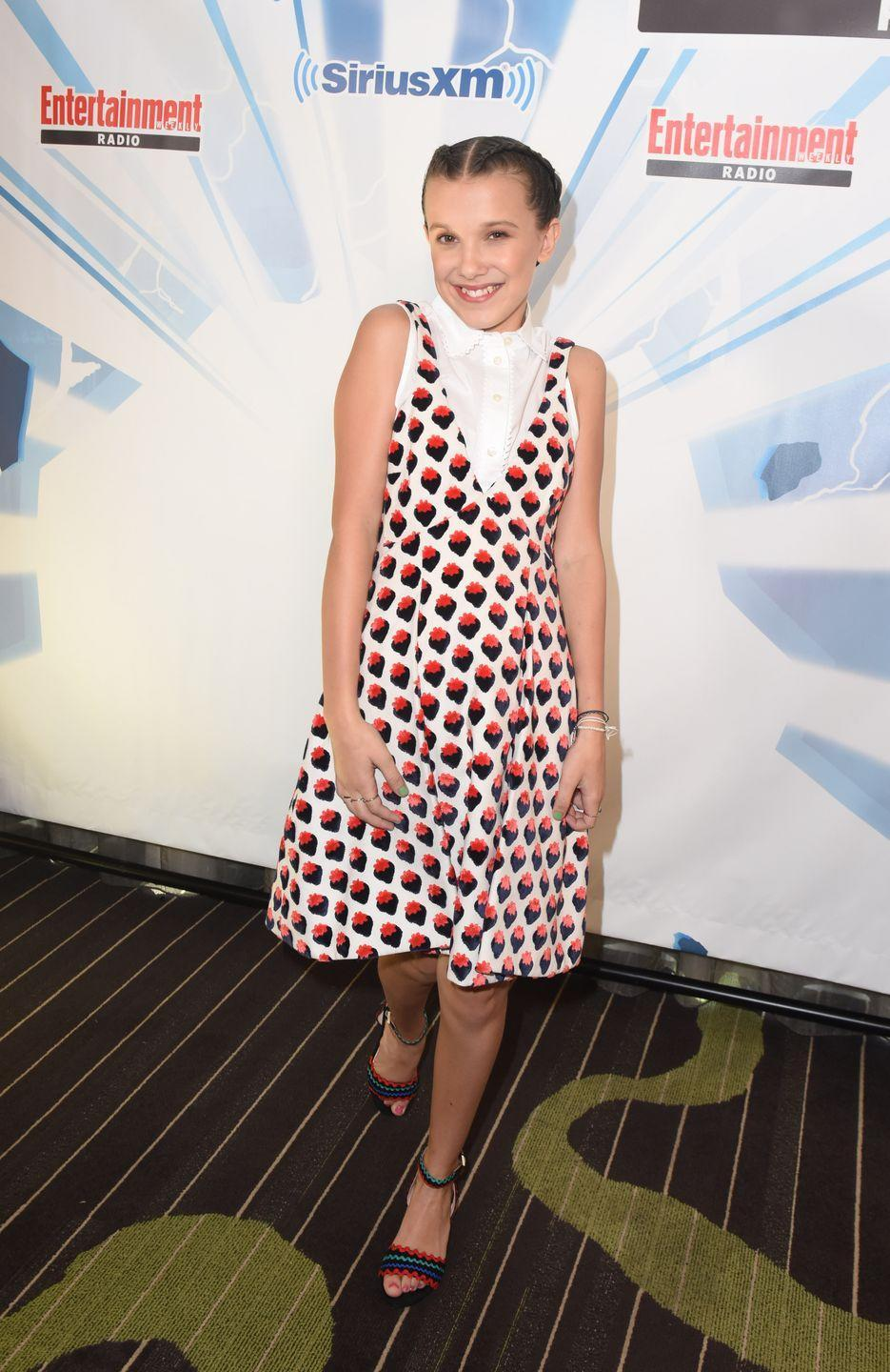 <p>I didn't realize I needed a strawberry print dress in my life until Millie Bobby Brown wore one with a button-up and striped heels. </p>