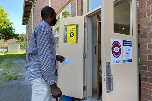 A man enters a polling station in the Halifax Needham riding on Aug. 17. Most polls will close at 8 p.m. but there are exceptions.  (Rose Murphy/CBC - image credit)