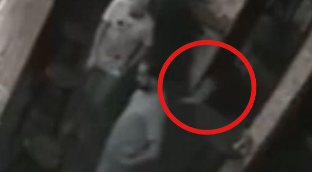 The little 'ghost' the men don't notice run past them. Photo: YouTube