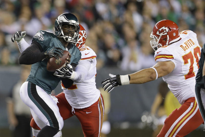 Philadelphia Eagles' Michael Vick, left, is cornered by Kansas City Chiefs' Tamba Hali and Mike DeVito during the first half of an NFL football game, Thursday, Sept. 19, 2013, in Philadelphia. (AP Photo/Matt Rourke)