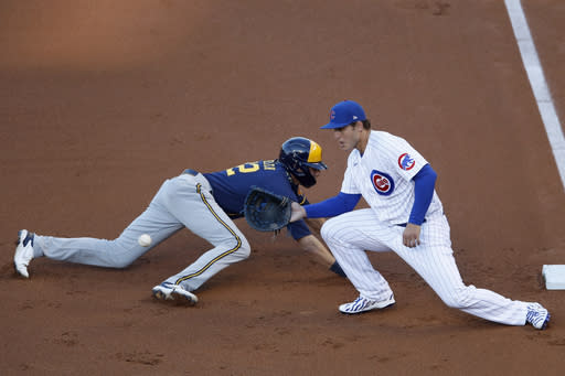 Chicago Cubs first baseman Anthony Rizzo, right, waits on the throw to first base as Milwaukee Brewers' Christian Yelich, left, dives back to the base during the first inning of a baseball game in Chicago, Thursday, Aug. 13, 2020. (AP Photo/Jeff Haynes)