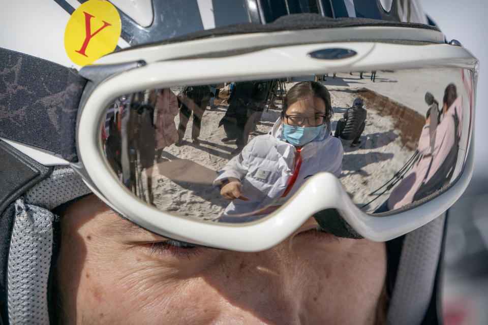 A staff member wearing a face mask to protect against the spread of the coronavirus is reflected in the goggles of a skier at the National Alpine Skiing Center in Yanqing on the outskirts of Beijing, Friday, Feb. 5, 2021. Beijing Olympic organizers showed off the downhill skiing venue and the world's longest bobsled and luge track Friday, one year ahead of the scheduled opening of the 2022 Olympic Winter Games. (AP Photo/Mark Schiefelbein)