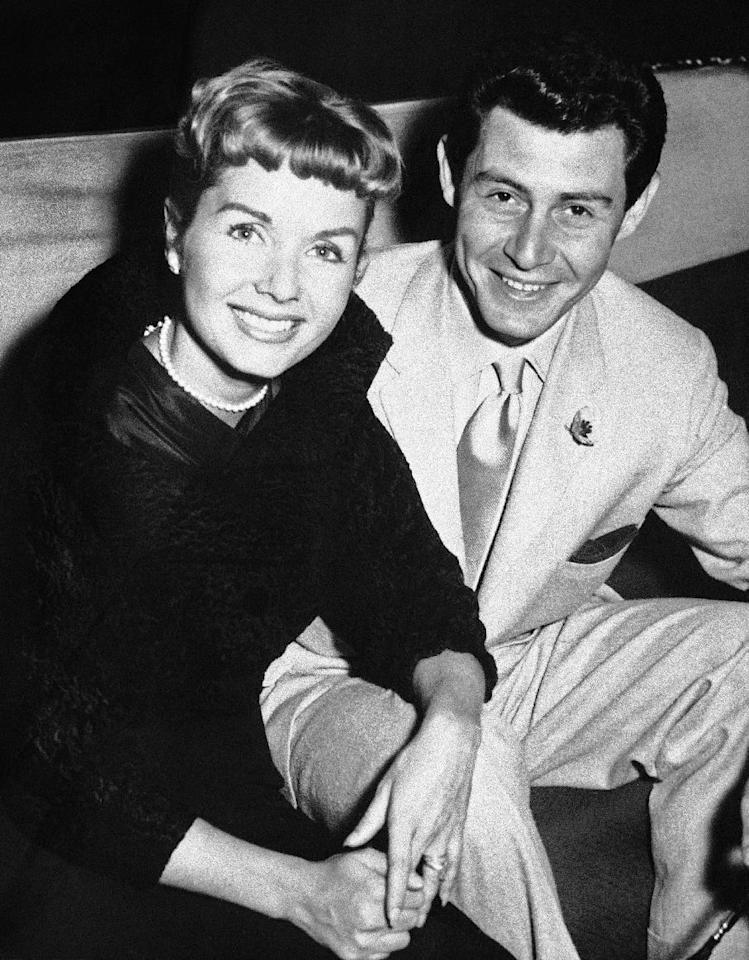 """File- This June 4, 1957, file photo shows Eddie Fisher and his wife Debbie Reynolds attending the reception at the Prince of Wales Theater, London. Reynolds herself has likened their split to the Jennifer Aniston-Angelina Jolie-Brad Pitt triangle, telling Vanity Fair last year: """"My three husbands all left me for another woman and obviously I wasn't a very sexual lady."""" (AP Photo/File)"""