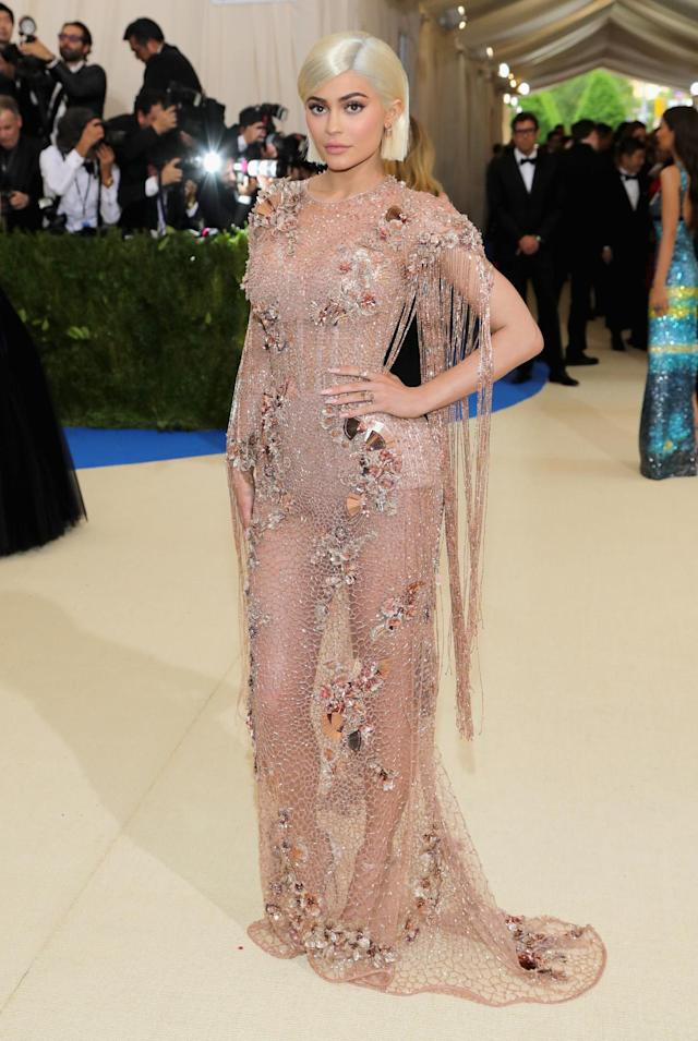 "<p>The social media star and makeup mogul wore a semi-sheer Atelier Versace gown. She opted for a platinum blonde wig for the event because, <a href=""https://www.instagram.com/p/BTknAQ2BrnT/?taken-by=kyliejenner"" rel=""nofollow noopener"" target=""_blank"" data-ylk=""slk:according to her Instagram"" class=""link rapid-noclick-resp"">according to her Instagram</a>, when ""donatella wants you to go blonde .. you go f***ing BLONDE."" (Photo by Neilson Barnard/Getty Images) </p>"
