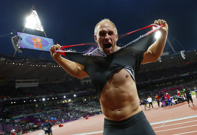 Germany's Robert Harting rips his shirt as he celebrates winning the men's discus throw final during the London 2012 Olympic Games at the Olympic Stadium August 7, 2012. Harting won gold ahead of Iran's Ehsan Hadadi who took silver and Estonia's Gerd Kanter who won bronze. REUTERS/Kai Pfaffenbach (BRITAIN - Tags: SPORT ATHLETICS OLYMPICS TPX IMAGES OF THE DAY)