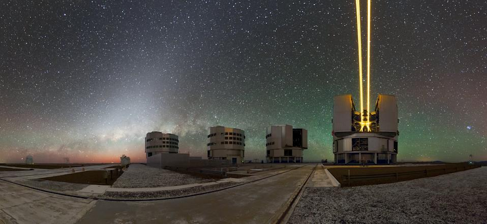 "Unit Telescope 4 of the Very Large Telescope at the European Southern Observatory in Chile fires its ""laser guide stars"" at the night sky as part of the telescope's adaptive optics system."