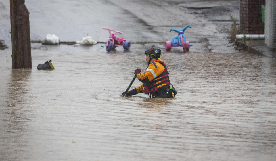 A member of a rescue team walks through a flooded street on Wednesday, Sept. 1, 2021, in Bridgeville, Pa. Pennsylvanians braced for downpours and high winds from the remnants of Hurricane Ida, with forecasters warning that creeks, streams and rivers would be inundated across the state's southern tier. (Andrew Rush/Pittsburgh Post-Gazette via AP)