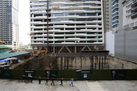 Construction workers, carrying steel bars, walk past a Century Spire advertisements at its construction site in Manila