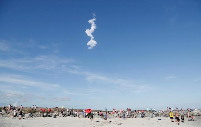 <p>The contrail of SpaceX's first Falcon Heavy rocket loom above spectators at Cocoa Beach after its launch from the Kennedy Space Center, Fla., Feb, 6, 2018. (Photo: Gregg Newton/Reuters) </p>
