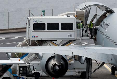 An injured German tourist involved in a bus accident, is helped onto a German Air Force medical airplane at Cristiano Ronaldo Airport in Funchal, on the island of Madeira, Portugal April 20, 2019. REUTERS/Rafael Marchante