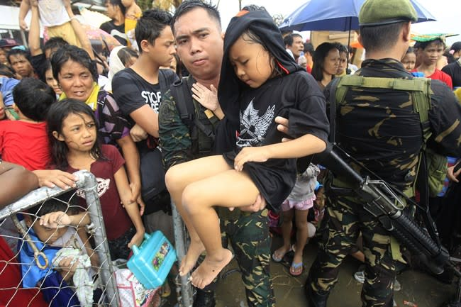 Typhoon survivors swarm airport, desperate to leave a city littered with bodies