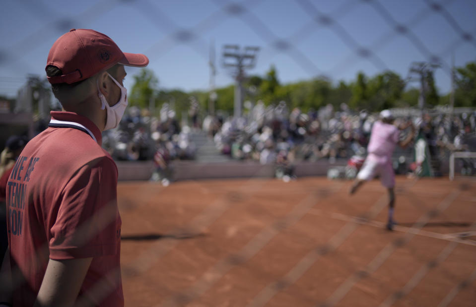 A court attendant wearing a face mask against the coronavirus watches as United States's Reilly Opelka plays a return to Slovakia's Andrej Martin during their first round match on on day two of the French Open tennis tournament at Roland Garros in Paris, France, Monday, May 31, 2021. (AP Photo/Christophe Ena)