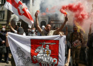 People, some of them ethnic Belarusians, light flares and wave Belarusian flags to support Belarusian opposition in front of Belarusian Embassy in Kyiv, Ukraine, Friday, Aug. 14, 2020. Crowds of protesters in Belarus swarmed the streets and thousands of workers rallied outside industrial plants to denounce a police crackdown on demonstrations over a disputed election that extended the 26-year rule of authoritarian President Alexander Lukashenko. (AP Photo/Efrem Lukatsky)