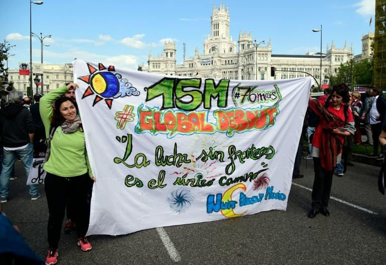 """Women carry a banner reading: """"The fight without frontiers is the only way"""" as they march during a demonstration marking the fifth anniversary of the """"Indignados"""" movement in Madrid, on May 15, 2016"""
