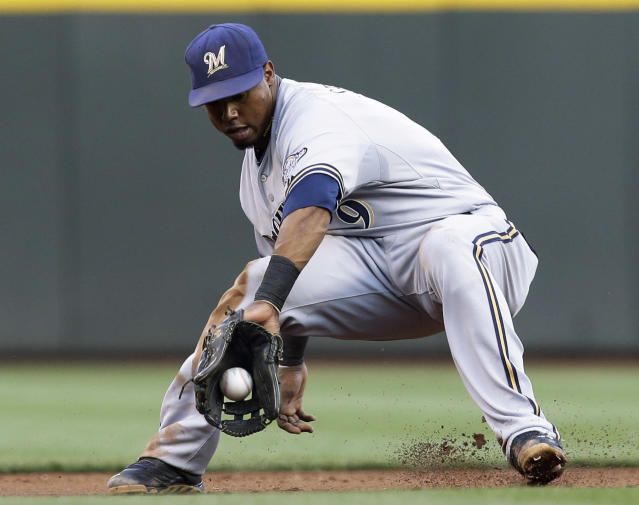 Milwaukee Brewers shortstop Jean Segura fields a ground ball hit by Cincinnati Reds' Brandon Phillips in the first inning of a baseball game, Friday, Aug. 23, 2013, in Cincinnati. Segura threw Phillips out at first. (AP Photo/Al Behrman)