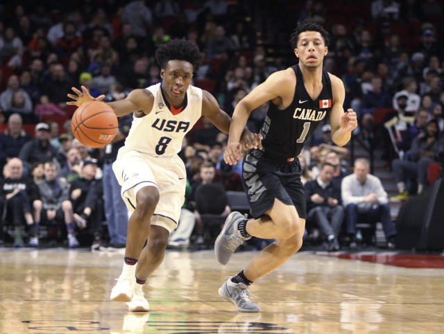 Team USA's Collin Sexton dribbles down the floor guarded by World Team's Lindell Wigginton during the first half of the Nike Hoop Summit basketball game in Portland, Ore., Friday, April 7, 2017. (Billy Gates/The Oregonian via AP)