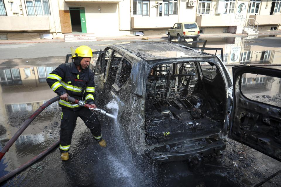 A firefighter extinguishes a burnt out car after multiple rocket system shelling by Armenian forces in Barda, Azerbaijan, Wednesday, Oct. 28, 2020. The Azerbaijani Defense Ministry rejected all the accusations and in turn accused Armenian forces of using the Smerch multiple rocket system to fire at the Azerbaijani towns of Terter and Barda. The strike on Barda killed more than 20 people and wounded 60, Azerbaijani officials said. (AP Photo/Aziz Karimov)