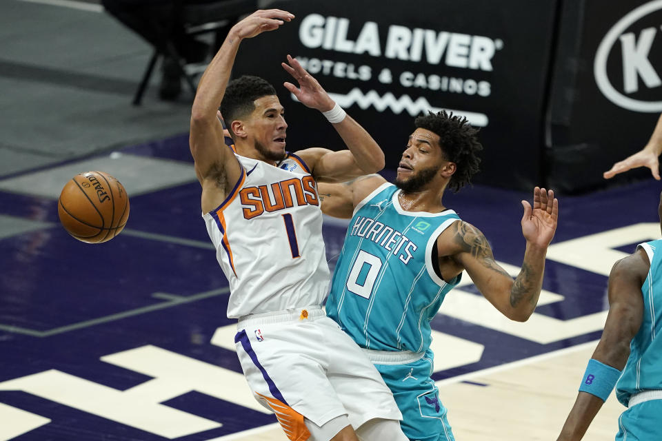 Charlotte Hornets forward Miles Bridges (0) knocks the ball loose from Phoenix Suns guard Devin Booker (1) during the first half of an NBA basketball game, Wednesday, Feb. 24, 2021, in Phoenix. (AP Photo/Matt York)