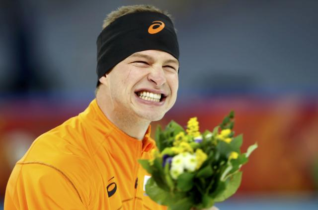 Sven Kramer of the Netherlands reacts after the flower ceremony after winning and setting an Olympic record time in his men's 5000 meters speed skating race during the 2014 Sochi Winter Olympics, February 8, 2014. REUTERS/Marko Djurica (RUSSIA - Tags: OLYMPICS SPORT SPEED SKATING TPX IMAGES OF THE DAY)
