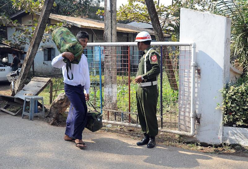 A former Myanmar child soldier (L) carries his belongings as he walks out from a military compound in Yangon on January 18, 2014