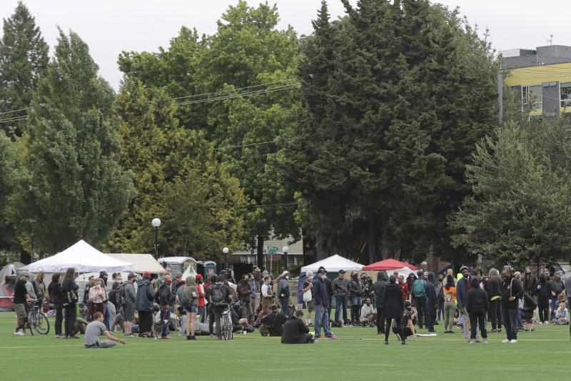 A meeting of protesters, organizers, and other is held, Saturday, June 20, 2020, in Cal Anderson Park in the Capitol Hill Occupied Protest zone in Seattle. A pre-dawn shooting near the area left one person dead and critically injured another person, authorities said Saturday. The area has been occupied by protesters after Seattle Police pulled back from several blocks of the city's Capitol Hill neighborhood near the Police Department's East Precinct building. (AP Photo/Ted S. Warren)