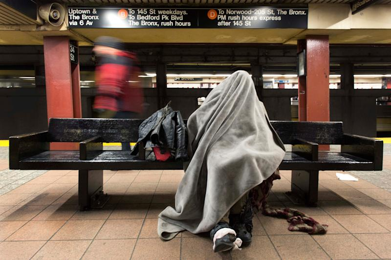 A homeless man rests under a blanket in a New York subway station.