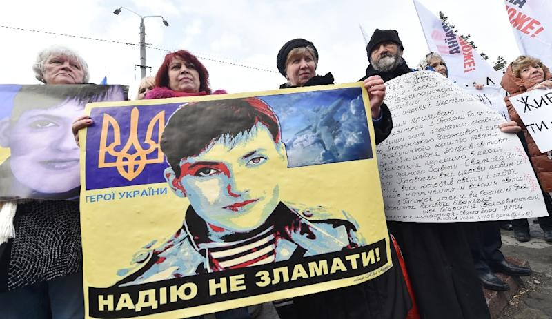 Protesters hold images of jailed female Ukrainian pilot Nadiya Savchenko during a rally in front of Russian embassy in Kiev on March 9, 2016 (AFP Photo/Sergei Supinsky)