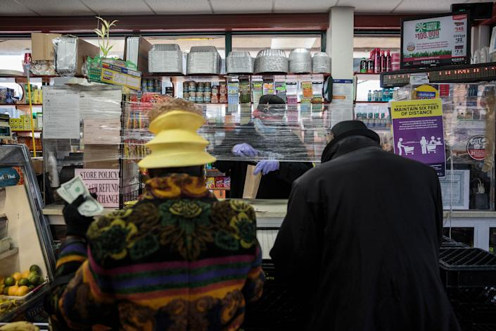 Blanche tries to buy batteries at the local convenience store after her radio stopped working on April 12. Most stores have been closed in the neighborhood, but the bodegas and hardware stores are open. | Sarah Blesener