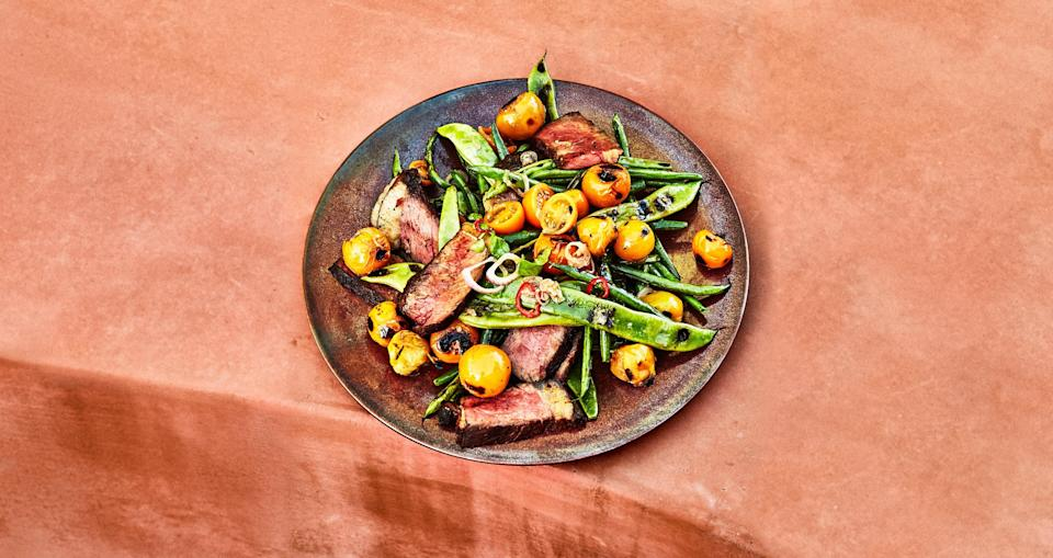 "For this grilled strip steak recipe, cooking half the tomatoes in a skillet placed on the grill lets you capture all their juices and turn them into a saucy condiment for the meat. <a href=""https://www.bonappetit.com/recipe/strip-steak-with-blistered-beans-and-tomatoes?mbid=synd_yahoo_rss"" rel=""nofollow noopener"" target=""_blank"" data-ylk=""slk:See recipe."" class=""link rapid-noclick-resp"">See recipe.</a>"