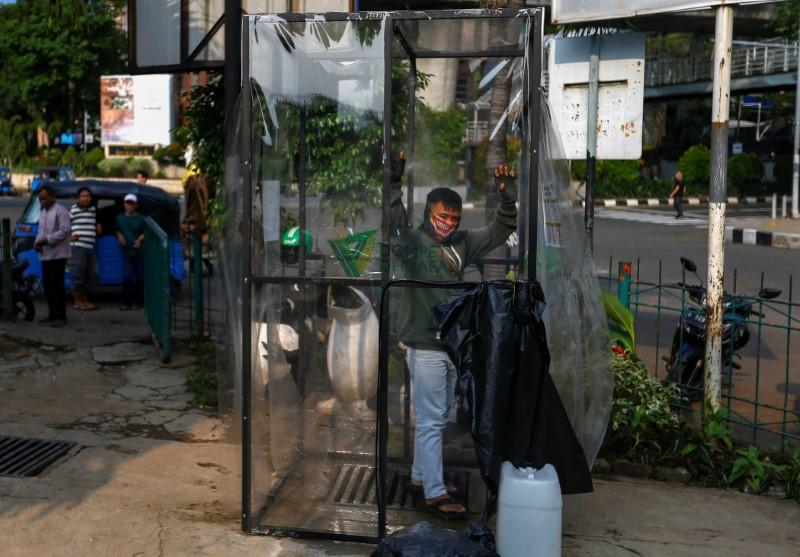 Man wearing a face mask is sprayed inside a disinfection chamber, outside a shopping mall in Jakarta