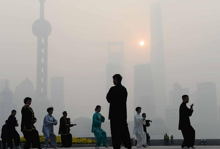 Residents exercise amid heavy smog on the Bund waterfront in Shanghai on November 12, 2014 (AFP Photo/)