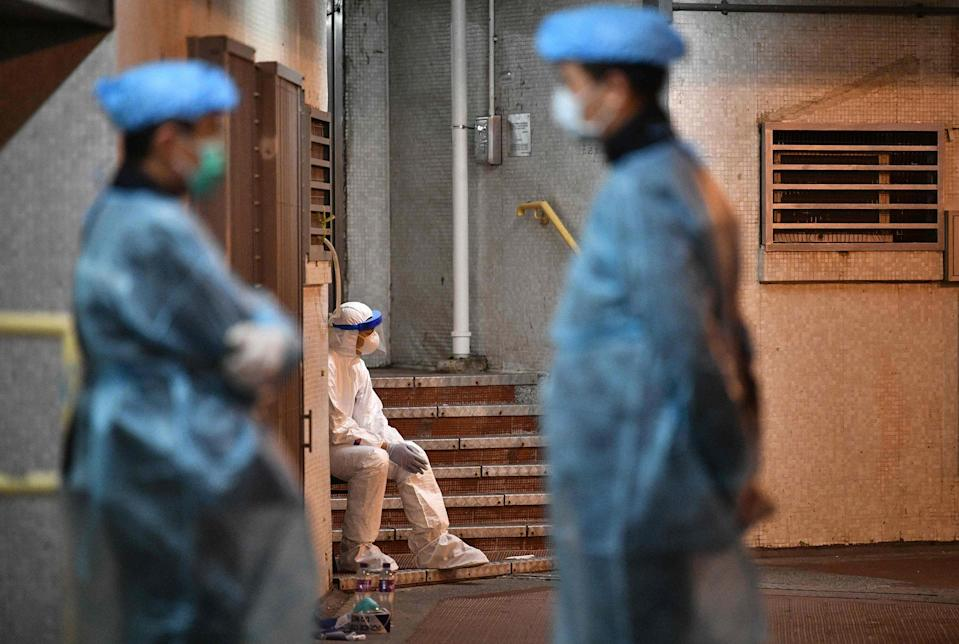Image: Medical personnel wearing protective suits stay near a block's entrance on the grounds of a residential estate in Hong Kong, early on Feb. 11, 2020.