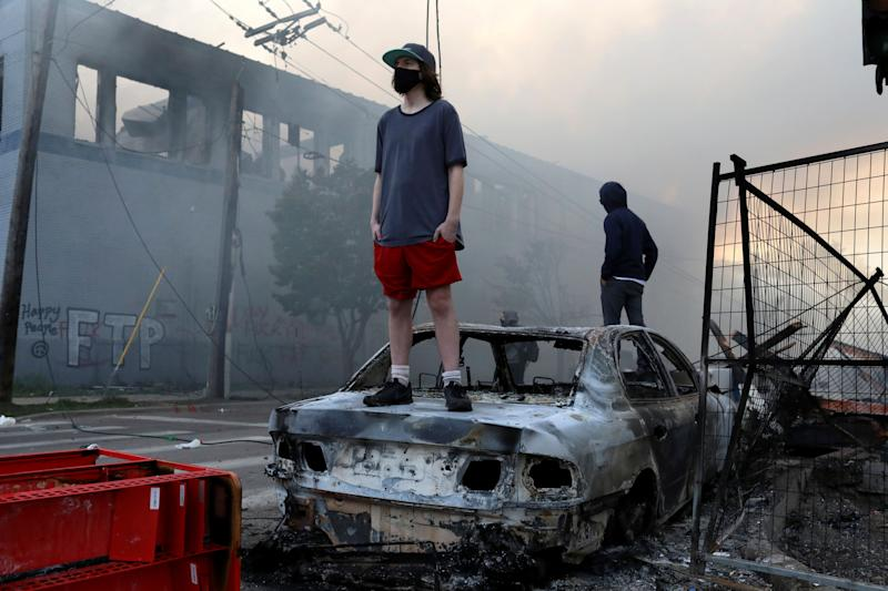 <strong>People stand on a burned up car as fires burn near a Target Store early Thursday.</strong> (Photo: ASSOCIATED PRESS)