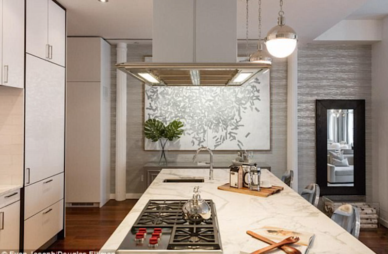 The open plan kitchen features porcelain countertops and white cabinetry and fit out with designer appliances. Source: Evan Joseph/Douglas Elliman