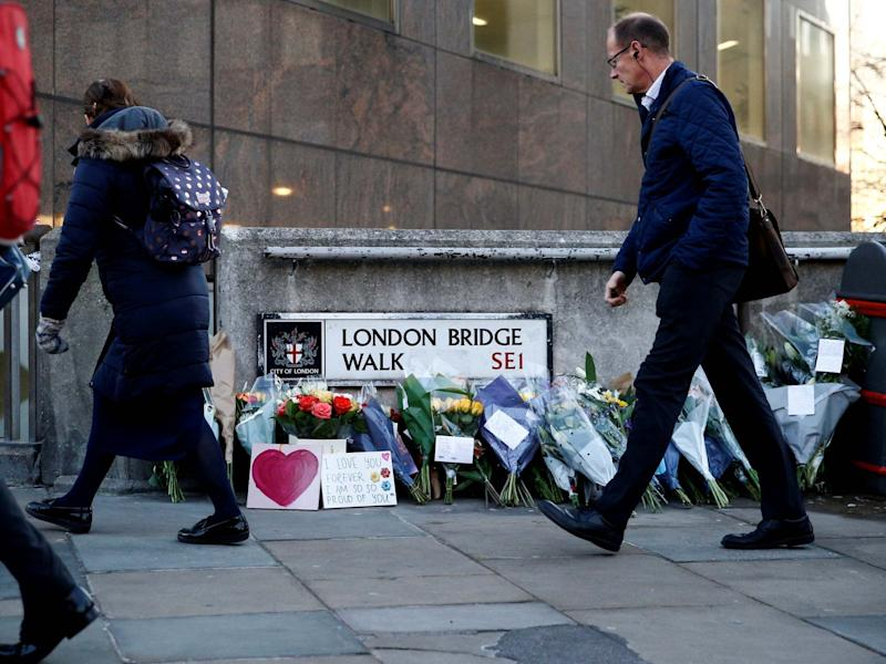 A commuter looks at flowers and signs left at the scene of the attack on London Bridge: Reuters