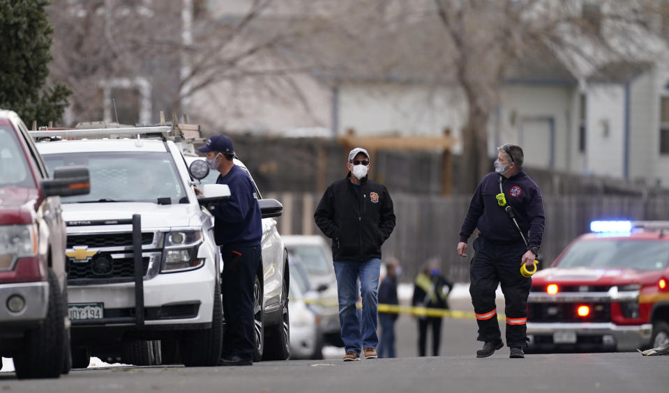 Fire officials walk up Elmwood Street to see where a piece of debris from a passenger airplane crushed a pickup truck parked next to a home in Broomfield, Colo., as the plane shed parts while making an emergency landing at nearby Denver International Airport Saturday, Feb. 20, 2021. (AP Photo/David Zalubowski)