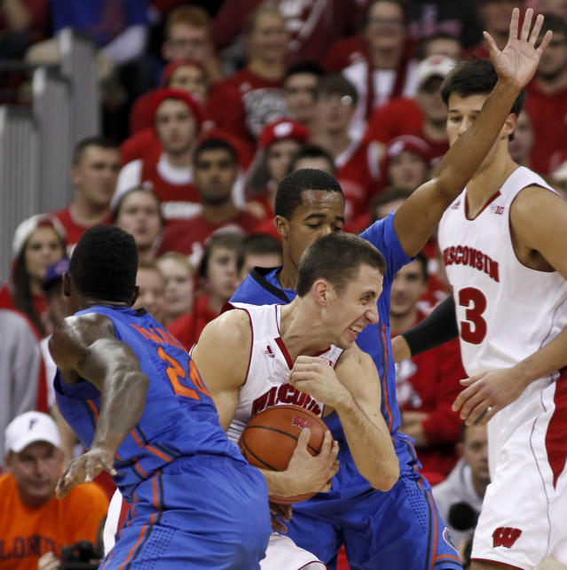 Wisconsin's Josh Gasser, center, drives between Florida's Casey Prather (24) and Kasey Hill during the first half of an NCAA college basketball game Tuesday, Nov. 12, 2013, in Madison, Wis. At right is Wisconsin Duje Dukan. (AP Photo/Andy Manis)