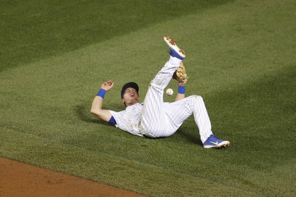 Chicago Cubs shortstop Nico Hoerner loses control of the ball on a base hit single off the bat of Milwaukee Brewers' Brock Holt during the fifth inning of a baseball game against the Milwaukee Brewers Friday, Aug. 14, 2020, in Chicago. (AP Photo/Jeff Haynes)