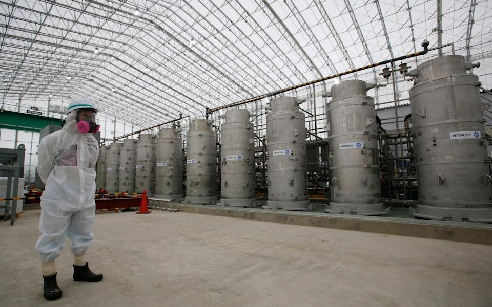A Tokyo Electric Power Co. (TEPCO) official wearing a radioactive protective gear stands in front of Advanced Liquid Processing Systems during a press tour at the Fukushima Dai-ichi nuclear power plant - AP Pool