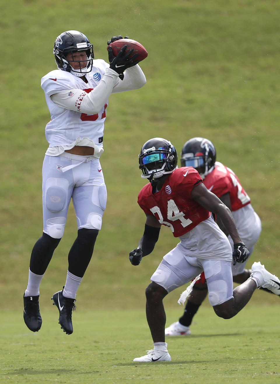 Atlanta Falcons tight end Austin Hooper (81) makes a catch as cornerback Brian Poole (34) defends during NFL football training camp, Tuesday, Aug. 7, 2018, in Flowery Branch, Ga. (AP Photo/John Bazemore)
