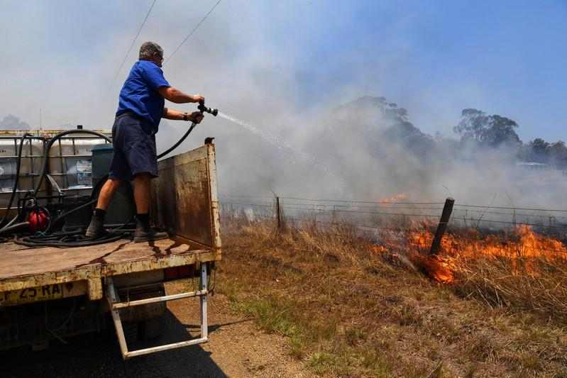 Tinonee resident Brian Acheson sets up his tip truck as a makeshift fire truck to assist residents fighting spot and grass fires in the Hillville area near Taree