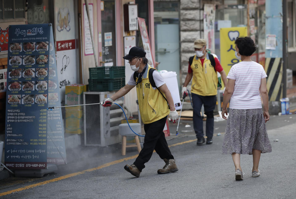 People disinfect as a precaution against the coronavirus in Seoul, South Korea, Saturday, Aug. 29, 2020. Health officials prepare to tighten distancing restrictions in the greater capital area. (AP Photo/Lee Jin-man)