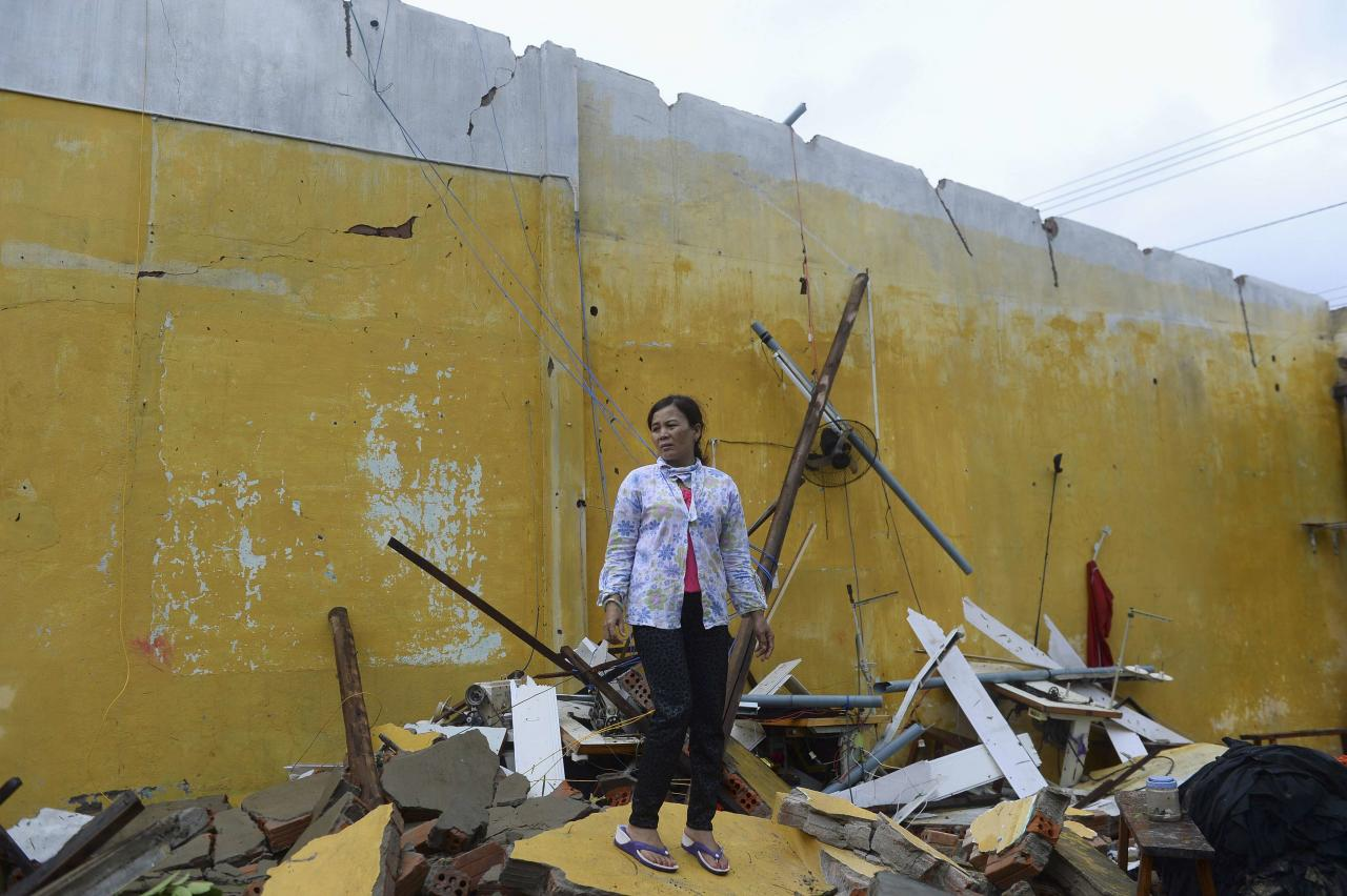 Nguyen Thi Linh stands among debris of her home, which collapsed due to Typhoon Nari, in Vietnam's central Quang Nam province, October 15, 2013. Typhoon Nari knocked down trees and damaged hundreds of houses in central Vietnam early on Tuesday, forcing the evacuation of tens of thousands of people, state media said. More than 122,000 people had been moved to safe ground in several provinces, including Quang Nam and Danang city, by late Monday before the typhoon arrived, the official Tuoi Tre (Youth) newspaper reported. REUTERS/Duc Hien (VIETNAM - Tags: DISASTER ENVIRONMENT TPX IMAGES OF THE DAY)