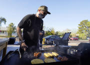 Chef Mike Winneker prepares food in front of his home Saturday, April 3, 2021, in Scottsdale, Ariz. Beaten down by the pandemic, many laid-off or idle restaurant workers have pivoted to dishing out food with a taste of home. Some have found their entrepreneurial side, slinging their culinary creations from their own kitchens. (AP Photo/Ross D. Franklin)