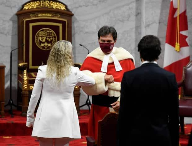 Gov. Gen. Julie Payette gives an elbow bump to Chief Justice Richard Wagner as she arrives with Prime Minister Justin Trudeau to deliver the throne speech in the Senate chamber in Ottawa on Wed. Sept. 23, 2020.