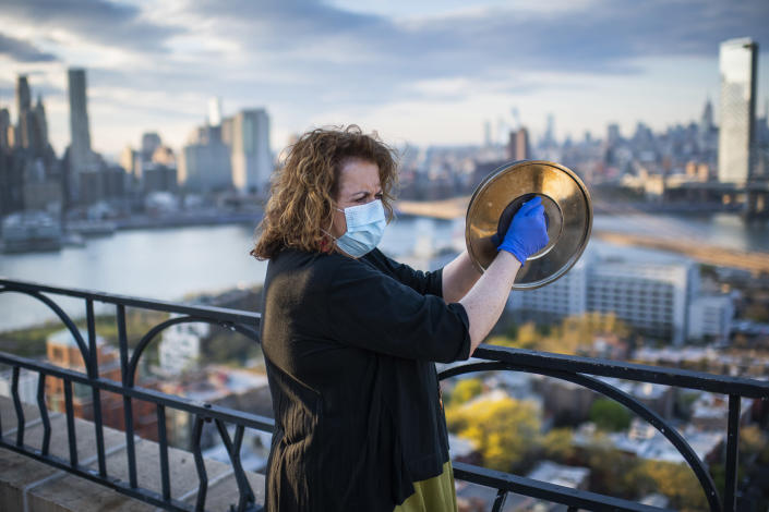 Laurie Garrett, a Pulitzer Prize-winning journalist, cheers essential workers from the roof of her apartment building, joining a citywide ritual every evening in New York, on April 28, 2020. (Joshua Bright/The New York Times)